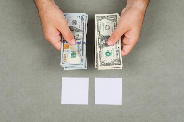 Zakelijke en boekhoudkundige concept met plaknotities, vergrootglas op grijze oppervlak plat lag. man met contant geld dollars.