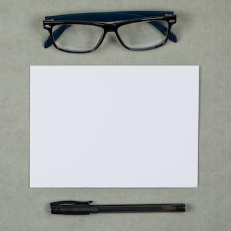 Zakelijke en financiële concept met glazen, pen, blanco papier op grijze achtergrond plat lag.