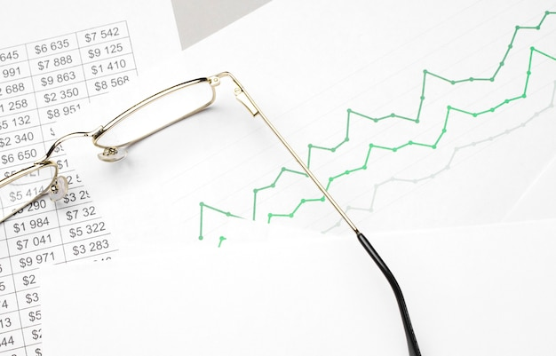 Zakelijke en financiële grafiek met bril en pen op witte ondergrond