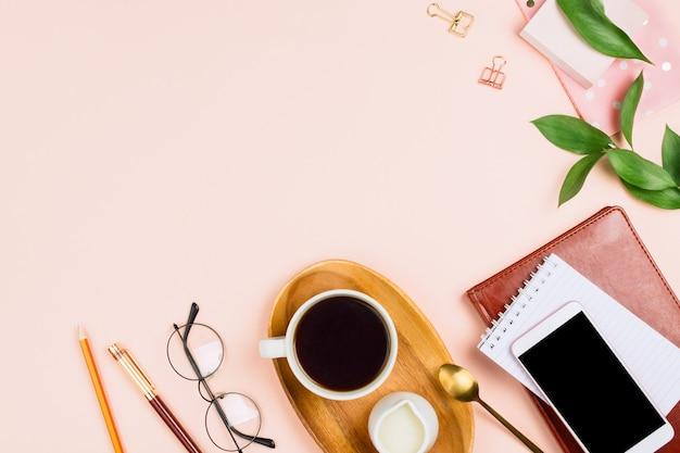 Zakelijke flatlay mockup met smartphone met zwarte copyspace scherm, kopje koffie op een houten bord, notebooks, glazen en andere accessoires op pastel achtergrond met copyspace