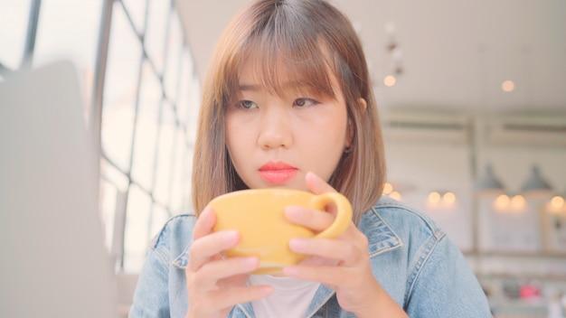 Zakelijke freelance aziatische vrouw die werkt, projecten op laptop doet en warme kop koffie drinkt terwijl het zitten op lijst in koffie.