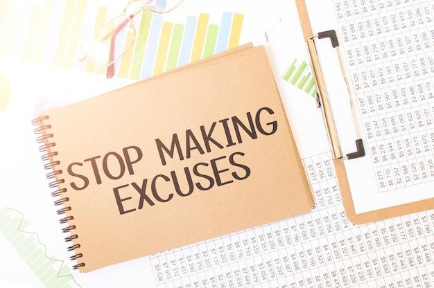 Zakelijke grafiek op een vel ambachtelijke kleur kladblok met stop making excuses-teken. kladblok op bureau met financiële documentatie