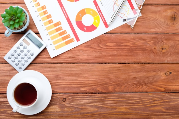 Zakelijke grafieken, koffie en computer op het bureaublad. zakelijke items op een houten achtergrond