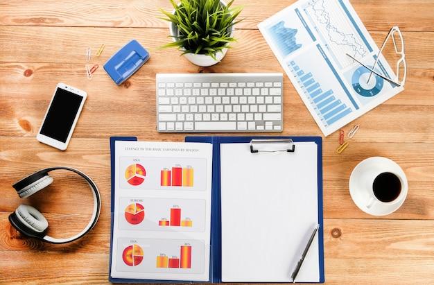 Zakelijke grafieken, koffie en computer op het bureaublad. zakelijke items op een houten tafel.
