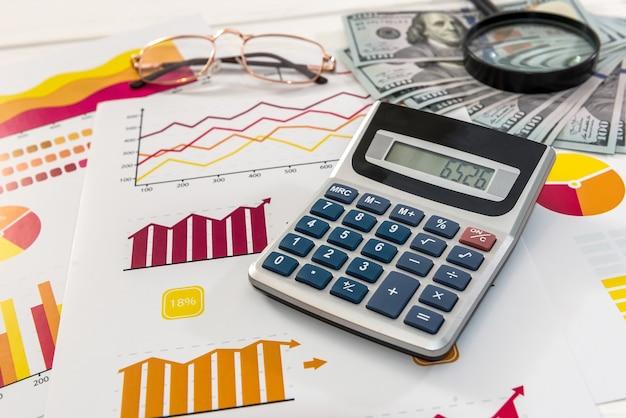 Zakelijke grafieken met rekenmachine en dollarbankbiljetten