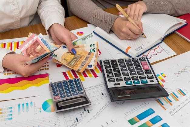 Zakelijke grafieken met vrouwelijke handen met eurobankbiljetten