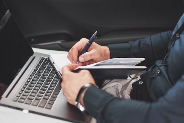 Zakelijke hand schrijven notities autostoel. voorbereiden op een vergadering