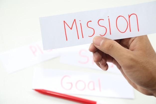 Zakelijke hand schrijven van een stuk missie papier