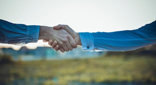 Zakelijke handdruk en mensen bedrijfsconcepten. twee mannen handen schudden op zonsondergang achtergrond.