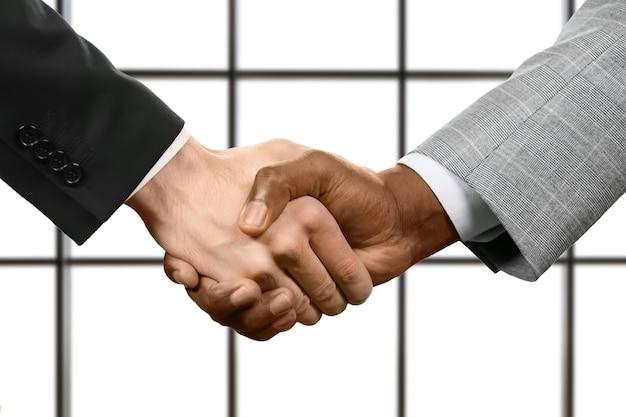 Zakelijke handdruk op witte achtergrond. zakenlieden handen schudden. onthoud uw beloften. respect en goedkeuring.