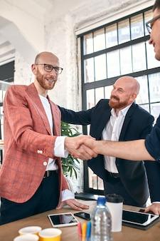 Zakelijke handdruk tijdens vergadering of onderhandeling op kantoor. partners zijn tevreden door het ondertekenen van een contract of financiële papieren. selectieve aandacht.