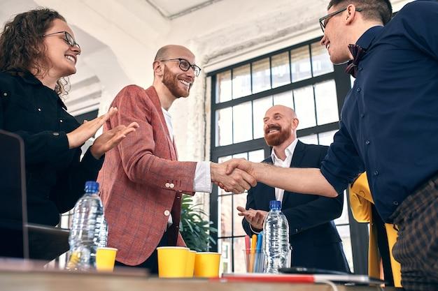 Zakelijke handdruk tijdens vergadering of onderhandeling op kantoor partners zijn tevreden omdat ze contract of financiële documenten ondertekenen