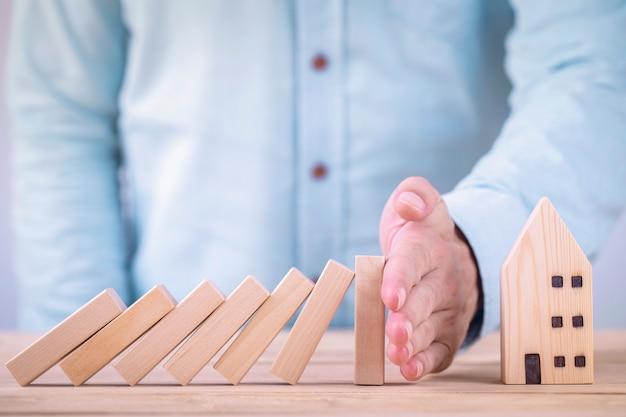 Zakelijke handen stoppen houten blokken van domino-effect voordat ze huis vernietigen, bescherming van privé-eigendom financieren van domino-effect concept