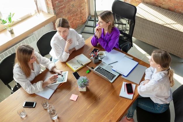 Zakelijke jonge blanke vrouw in moderne kantoor met team