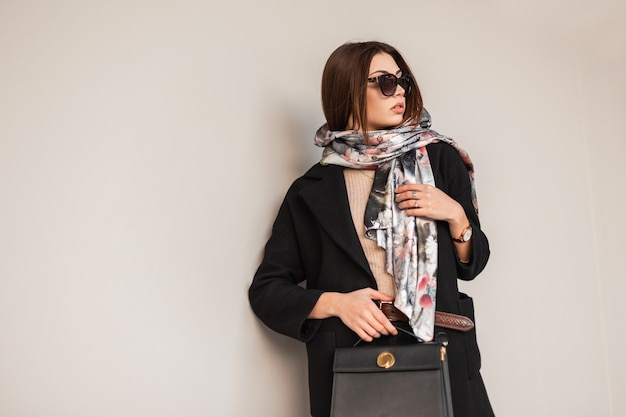 Zakelijke jonge brunette vrouw in stijlvolle zonnebril in een zwarte jas met een modieuze lederen handtas in een elegante sjaal poseren in de buurt van een vintage muur op straat. mooi trendy meisje. schoonheidsdame.