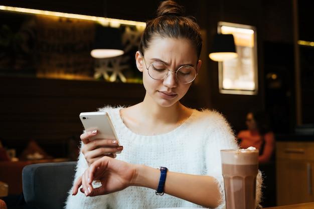 Zakelijke jonge meid freelancer met bril houdt smartphone vast en kijkt naar de klok