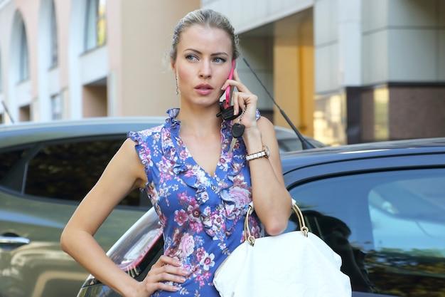 Zakelijke jonge mooie vrouw praten over de telefoon in de buurt van de auto