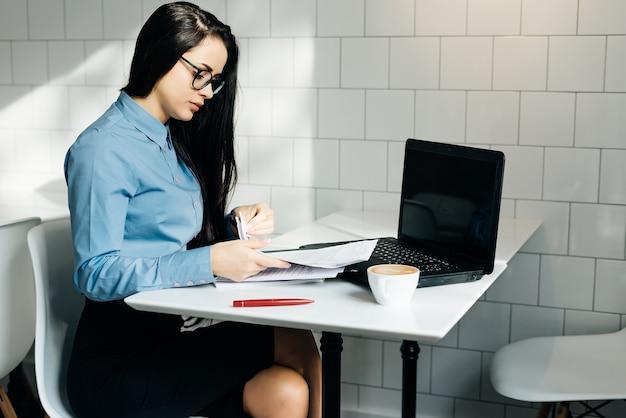 Zakelijke jonge studente in blauw shirt en bril die op laptop in café werkt