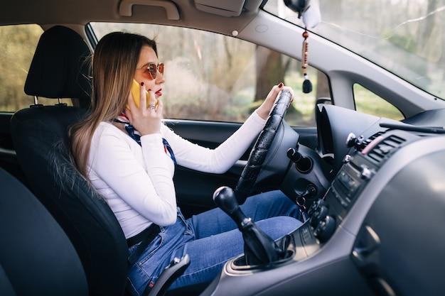 Zakelijke jonge vrouw auto rijden en praten op mobiele telefoon concentreren op de weg
