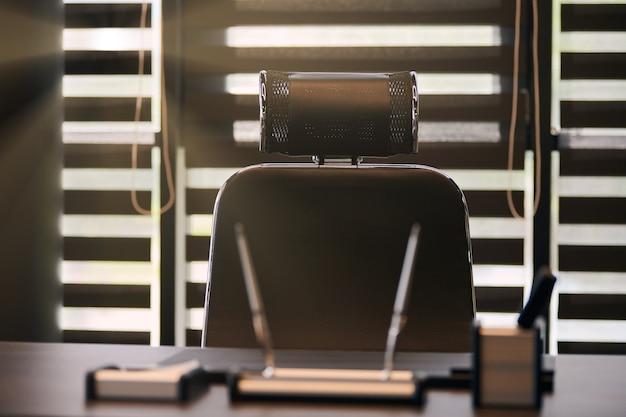 Zakelijke kantoor werkplek. zonlicht op de werkplek voor chef, baas of andere werknemers. tafel en comfortabele stoel. licht door de half open jaloezieën