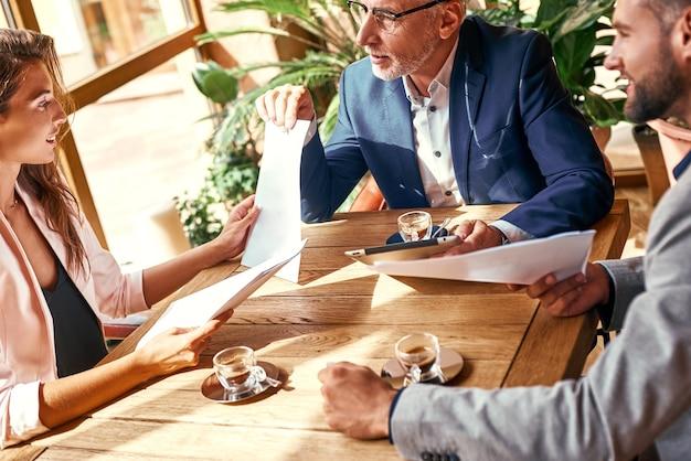 Zakelijke lunch drie mensen in het restaurant zitten aan tafel brainstormen werken aan project