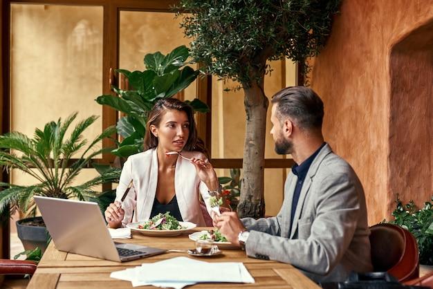 Zakelijke lunch man en vrouw zitten aan tafel in restaurant eten gezonde verse salade bespreken