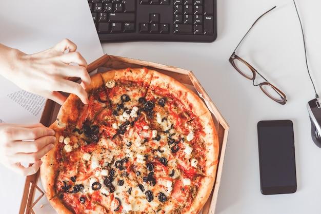 Zakelijke lunch op de werkplek. vegetarische pizza delen