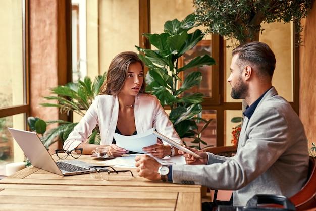 Zakelijke lunch zakenmensen zitten aan tafel in restaurant kijken elkaar aan het bespreken