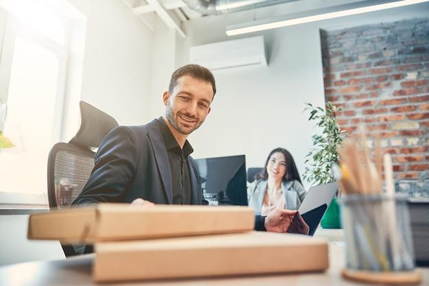 Zakelijke man en vrouw collega die samenwerken gebruiken computer tijdens bijeenkomst op kantoor