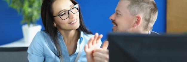Zakelijke man en vrouw communiceren aan de balie in kantoor