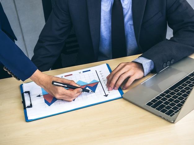 Zakelijke man en vrouw handen controleren rapport grafiek en notebook computer op bureau, vergadering en samen te werken in kantoor.