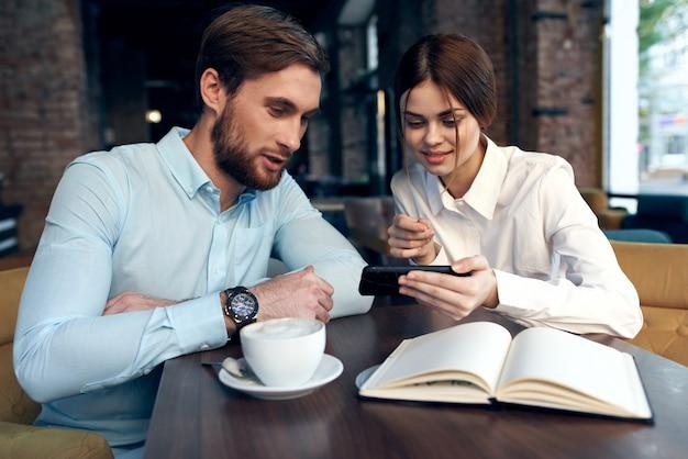 Zakelijke man en vrouw kijken naar de collega's van de telefooncommunicatie