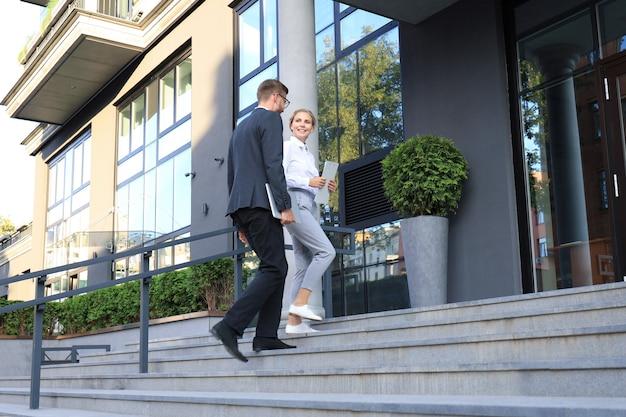 Zakelijke man en vrouw lopen in het kantoorcentrum.
