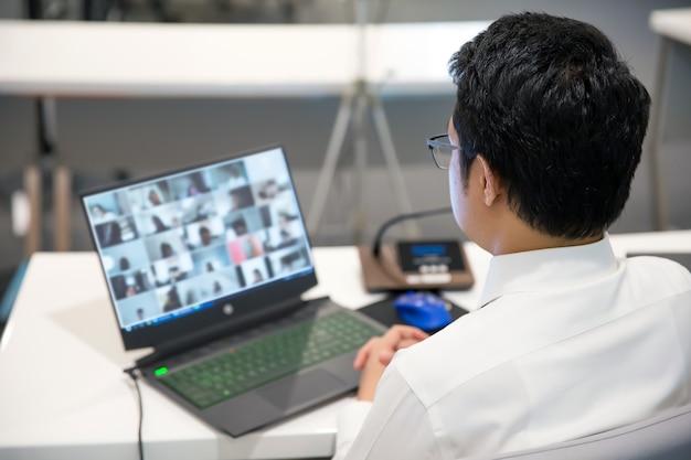 Zakelijke man gebruikt computer om team te ontmoeten met video-oproepprogramma.