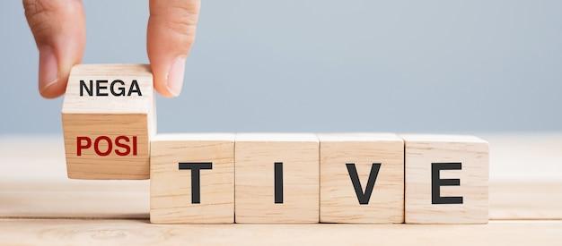 Zakelijke man hand met houten kubus met flip blok negatief naar positief woord op tabelachtergrond. kans, kans, mentaliteit, houding en positief denken concepten