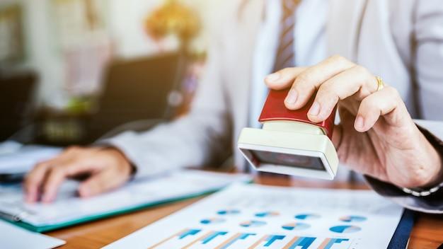 Zakelijke man handstempel document papier voor goed te keuren.