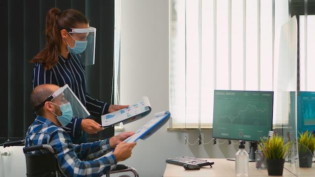 Zakelijke mensen die een beschermend masker dragen in een nieuwe normale strategie voor het maken van kantoren, zakenman zittend in een rolstoel team dat werkt in een professionele werkruimte in een bedrijfsbedrijf tijdens de covid-19 pandemie.