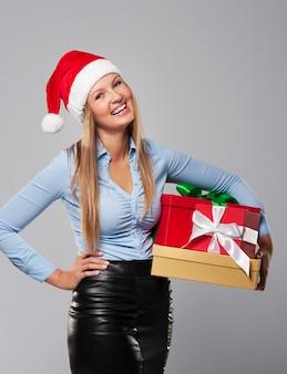 Zakelijke mevrouw claus met stapel kerstcadeau
