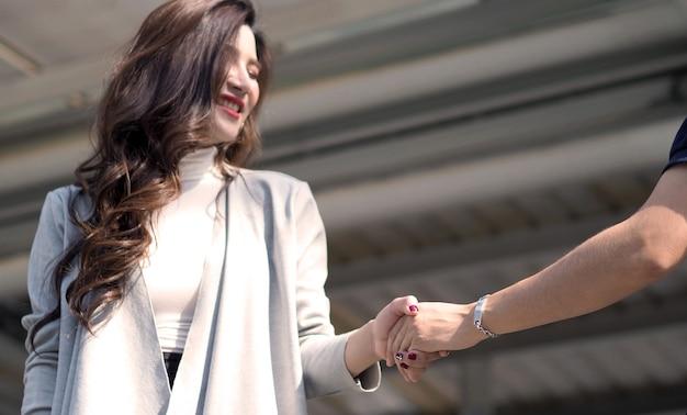 Zakelijke moderne vrouw die hand schudt met haar partner en glimlacht met voldoening na samenwerkingsovereenkomst
