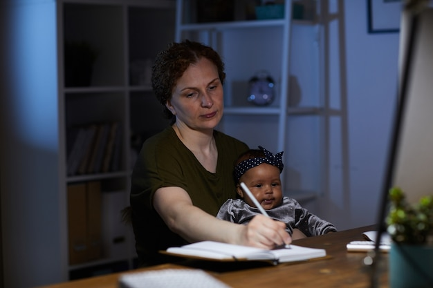Zakelijke moeder maken van aantekeningen in notitieblok zittend op haar werkplek met baby die ze tot 's nachts werkt