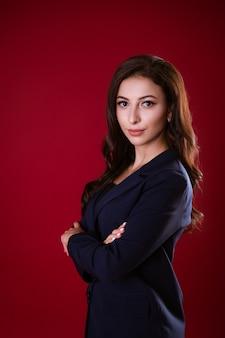 Zakelijke mooie vrouw in pak poseren op rode achtergrond