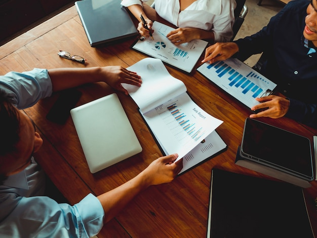 Zakelijke ontwerper houdt een pen om een succesvolle grafiek van het beleggingsinkomen te schrijven.