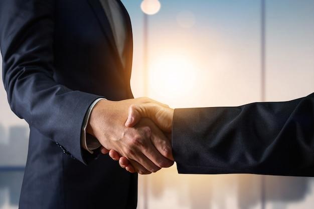 Zakelijke overeenkomst en succesvol onderhandelingsconcept, zakenman in de hand van de kostuumschok met klant