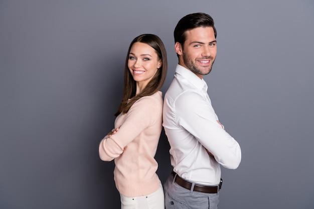 Zakelijke paar man vrouw gevouwen armen poseren op grijze muur