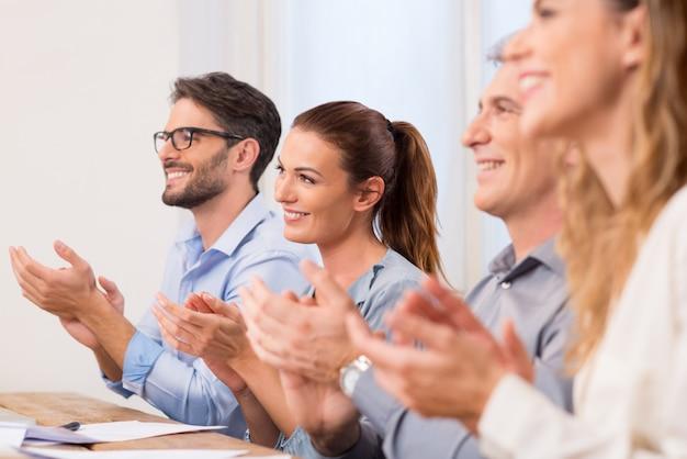Zakelijke partners applaudisseren tijdens de vergadering in een rij. succesvolle zakenmensen applaudisseren na presentatie. de gelukkige groep van het commerciële team klappen dient directiekamer in.