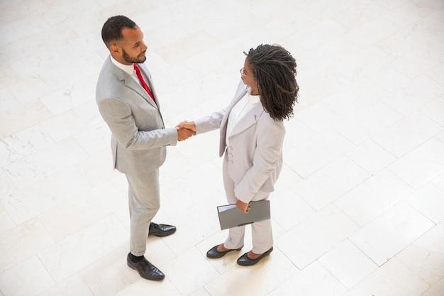 Zakelijke partners begroeten elkaar in kantoor gang