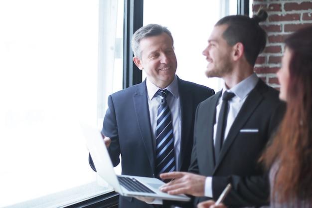 Zakelijke partners bespreken de voorwaarden van het contract, staande in functie