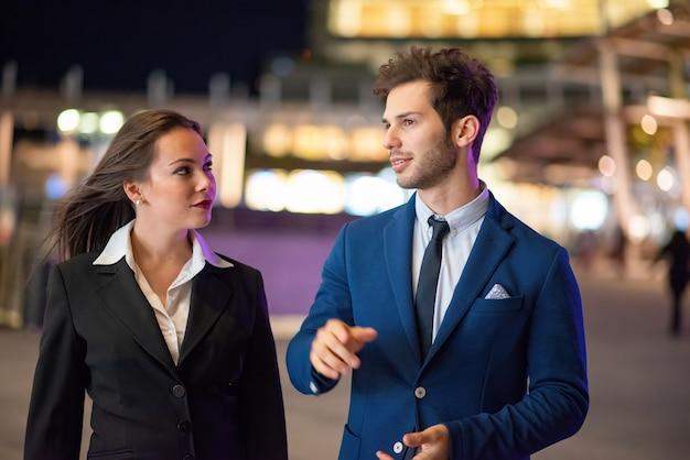 Zakelijke partners bespreken laat in de avond samen in een moderne stadsomgeving