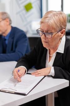 Zakelijke partners bespreken nieuw project voor bedrijfsevolutie, senior managervrouw die taken controleert