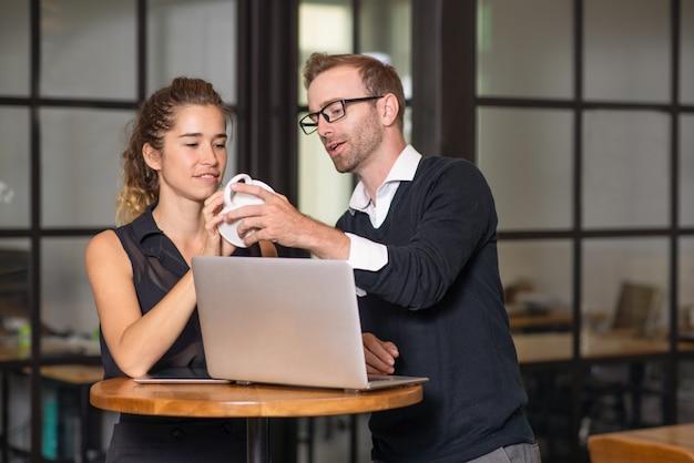 Zakelijke partners chatten en werken aan cafe tafel.